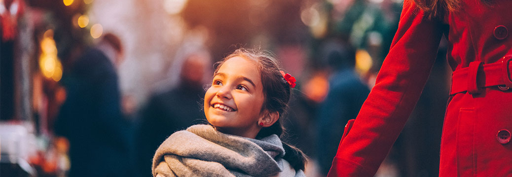 Small girl smiling while walking through a Christmas market.